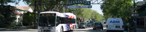 American flag bus under Pleasanton sign
