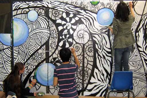 People painting mural on bus shelter