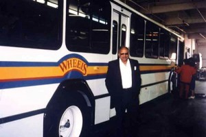Wheels bus with man standing by it