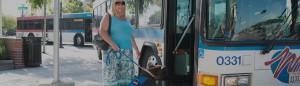 Woman boarding Wheels bus with service dog
